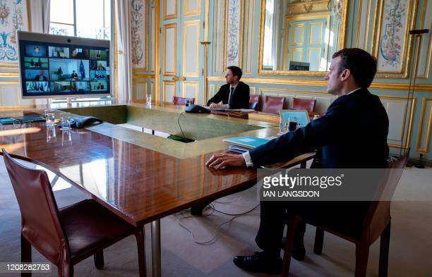 French President Emmanuel Macron attends a video conference call with members of the European Council at the Elysee Palace in Paris on March 26 to...