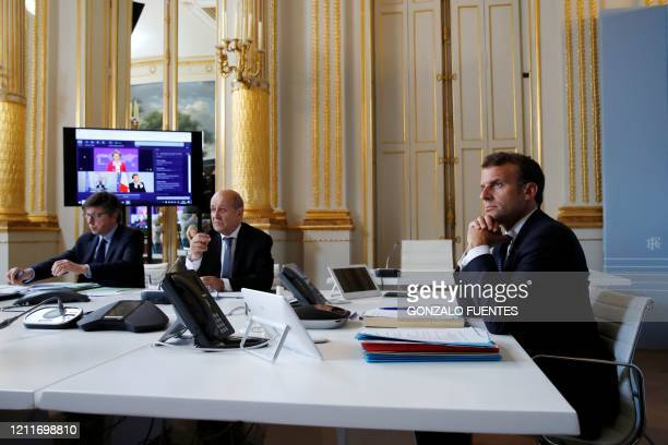 French President Emmanuel Macron attends an international videoconference on vaccination with French Foreign Affairs Minister Jean-Yves Le Drian at...