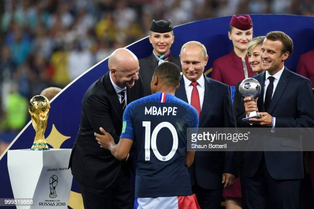 French President Emmanuel Macron awards Kylian Mbappe of France with the FIFA Young Player Award following the 2018 FIFA World Cup Final between...