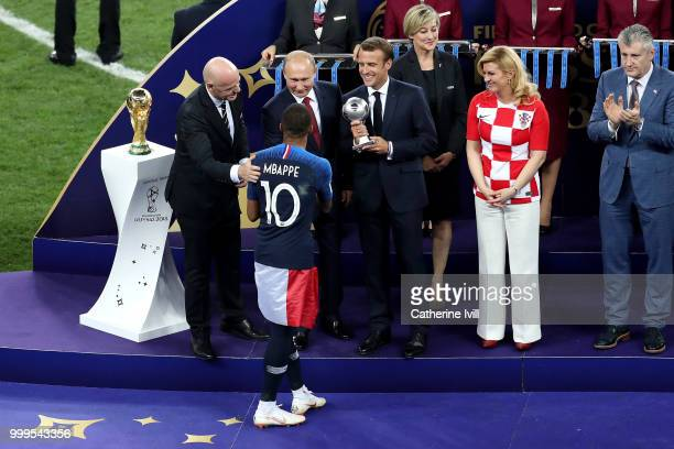 French President Emmanuel Macron awards Kylian Mbappe of France with the FIFA Young Player Award as FIFA President Gianni Infantino President of...