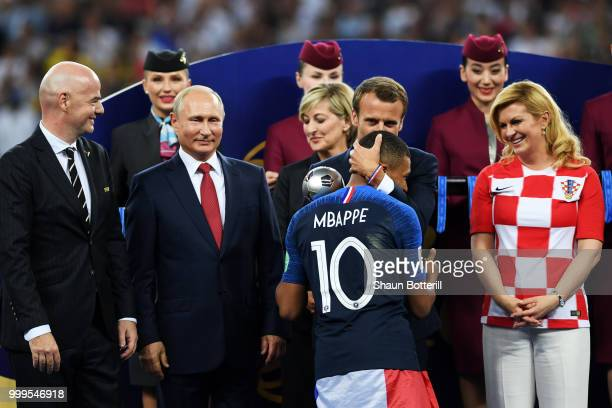 French President Emmanuel Macron awards Kylian Mbappe of France with the FIFA Young Player Award as President of Russia Vladimir Putin and President...