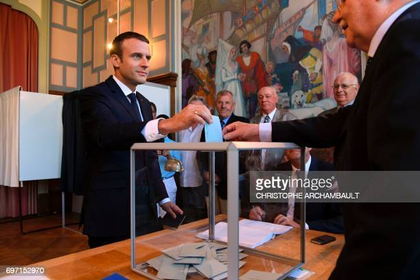 TOPSHOT French President Emmanuel Macron casts his ballot as he votes at a polling station in Le Touquet northern France during the second round of...