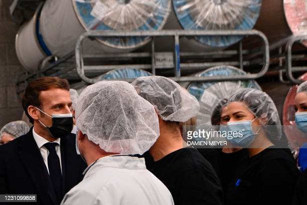 French president Emmanuel Macron chats with Aplix employees as he visits the French hook and loop fastening systems company Aplix in Le Cellier,...