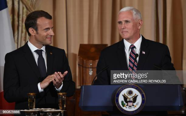 French President Emmanuel Macron claps as US Vice President Mike Pence looks on during a luncheon at the US State Department in Washington DC on...