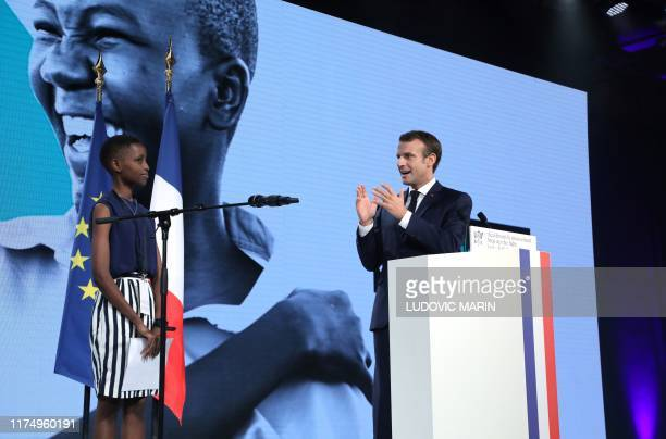 French president Emmanuel Macron congratulates Burundi's Amanda Dushime who comes to testify about her HIV sickness in Lyon, central eastern France,...