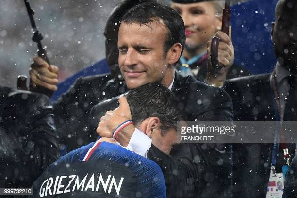 TOPSHOT French President Emmanuel Macron congratulates France's forward Antoine Griezmann during the trophy ceremony after winning the Russia 2018...