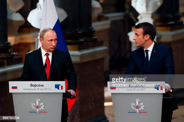 French President Emmanuel Macron delivers a joint press conference with Russian President Vladimir Putin following their meeting at the Versailles...