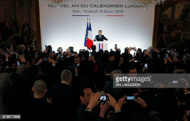 French President Emmanuel Macron delivers a speech in front of members of the Chinese community living in France who take pictures with smartphones...