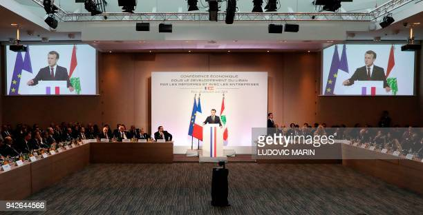 French President Emmanuel Macron delivers a speech next to Lebanese Prime Minister Saad Hariri during the international CEDRE conference in Paris on...