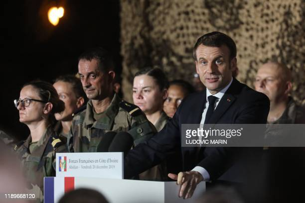 French President Emmanuel Macron delivers a speech to French soldiers at the Port-Bouet military camp prior to Christmas diner with the troupes on...