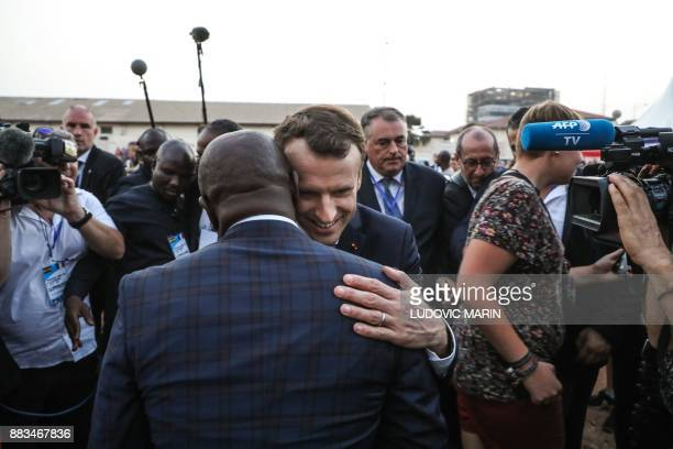 French President Emmanuel Macron embraces former Ghanaian football player Abedi Pele within a meeting with young members of a female football club in...