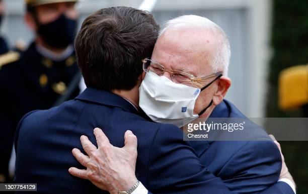 French President Emmanuel Macron embraces Israeli President Reuven Rivlin prior to their meeting at the Elysee Presidential Palace on March 18, 2021...