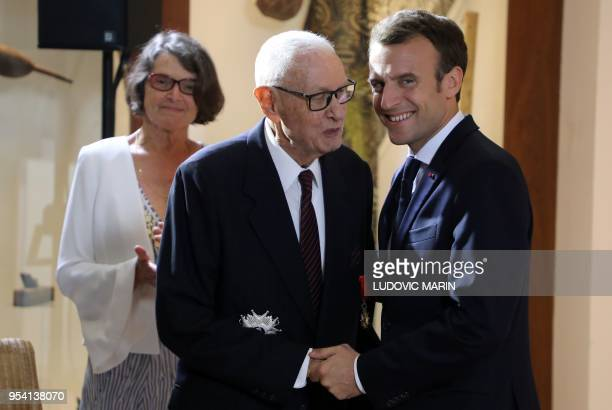 French President Emmanuel Macron embraces the former Mayor of Noumea Jean Leques after decorating him with The Grand Croix of the legion of honour at...