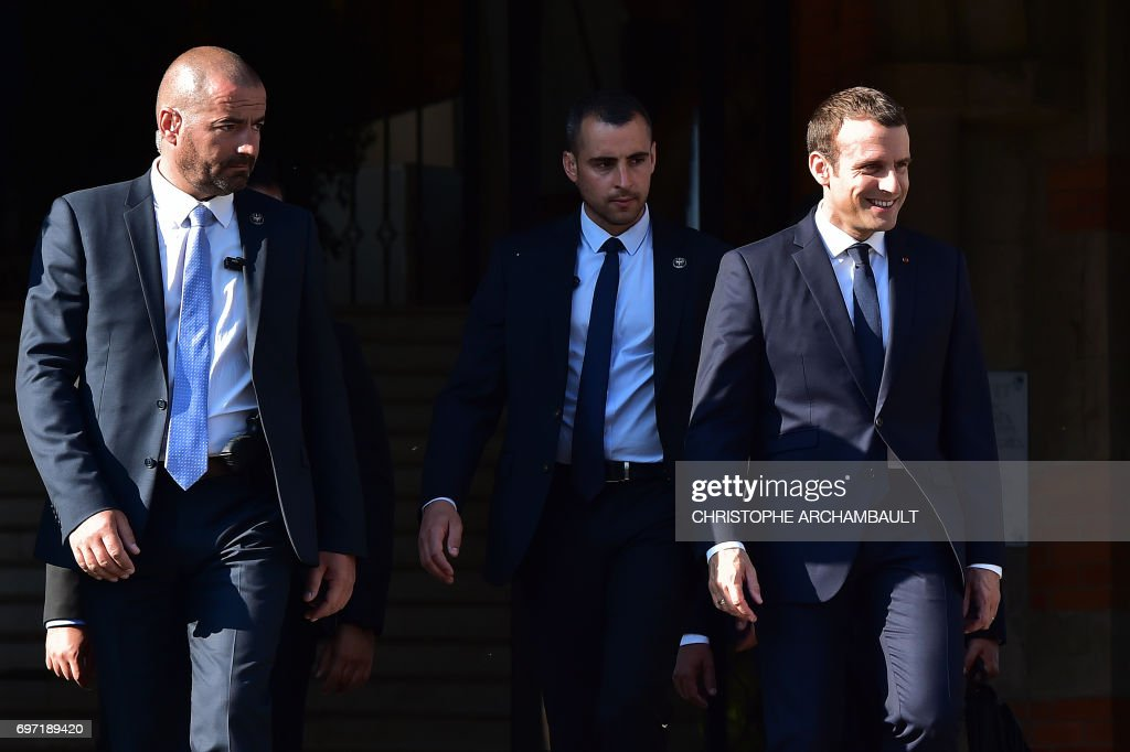 French President Emmanuel Macron (R), escorted by his bodyguards, leaves after voting at a polling station in Le Touquet, northern France, during the second round of the French parliamentary elections (elections legislatives in French), on June 18, 2017. /