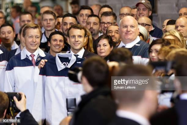 French President Emmanuel Macron flanked by Didier Leroy TMC vicepresident and factory's Director Luciano Biondo holds up a Toyota shirt as he visits...