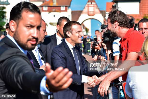 French President Emmanuel Macron flanked by Elysee senior security officer Alexandre Benalla shakes hands with people after he voting in Le Touquet...
