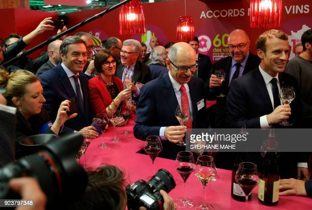 French President Emmanuel Macron flanked by French Agriculture Minister Stephane Travert holds a glass of white wine as he visits the 55th...