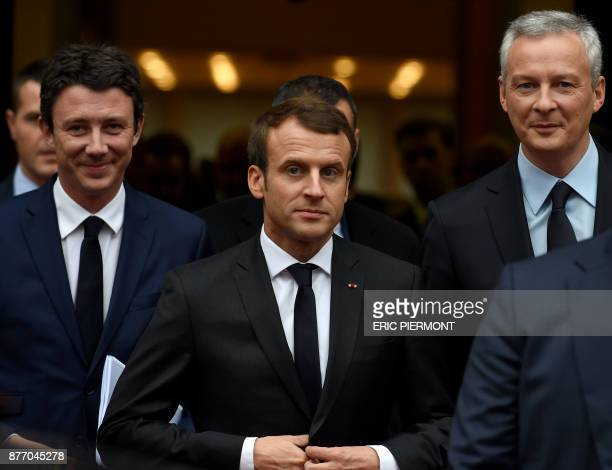 French President Emmanuel Macron flanked by French Economy Minister Bruno Le Maire and French Junior Minister for Economy Benjamin Griveaux leaves...
