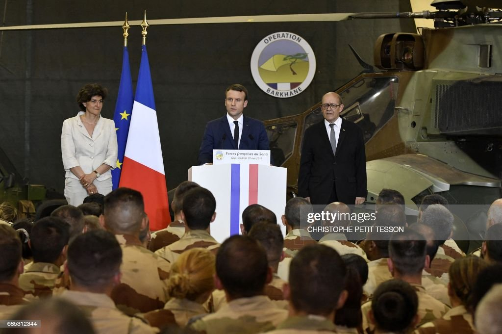 French President Emmanuel Macron (C), flanked by French Foreign Affairs Minister Jean-Yves Le Drian (R) and Defence minister Sylvie Goulard (L), makes his speech during his visit to the troops of France's Barkhane counter-terrorism operation in Africa's Sahel region in Gao, northern Mali, on May 19, 2017. French President Emmanuel Macron arrived on May 19 in conflict-torn Mali to visit French troops fighting jihadists on his first official trip outside Europe since taking power. /