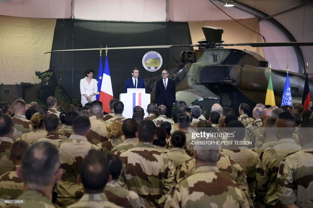 French President Emmanuel Macron (C), flanked by French Foreign Affairs Minister Jean-Yves Le Drian (R) and Defence minister Sylvie Goulard (L), speaks during his visit to the troops of France's Barkhane counter-terrorism operation in Africa's Sahel region in Gao, northern Mali, on May 19, 2017. French President Emmanuel Macron arrived on May 19 in conflict-torn Mali to visit French troops fighting jihadists on his first official trip outside Europe since taking power. /