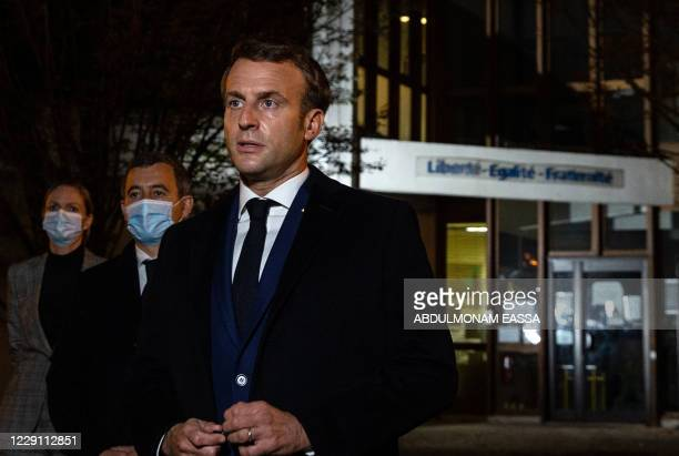 French President Emmanuel Macron , flanked by French Interior Minister Gerald Darmanin , speaks to the press in front of a middle school in Conflans...