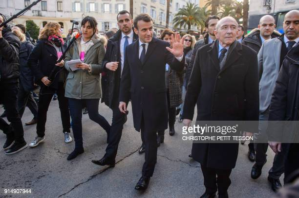 French President Emmanuel Macron flanked by French Minister of the Interior Gerard Collomb walk between the prefecture and the city hall of Ajaccio...