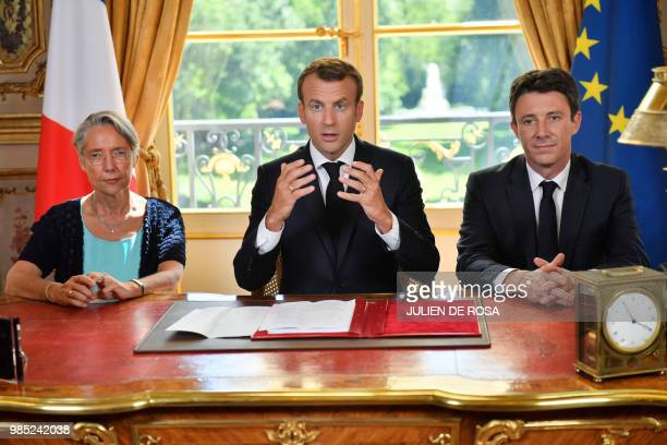 French President Emmanuel Macron flanked by French Transports Minister Elisabeth Borne and French government spokesman Benjamin Griveaux speaks to...
