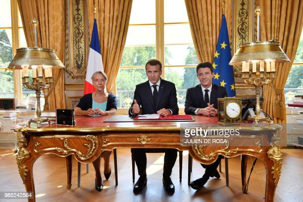 French President Emmanuel Macron , flanked by French Transports Minister Elisabeth Borne and French government spokesman Benjamin Griveaux, speaks to...