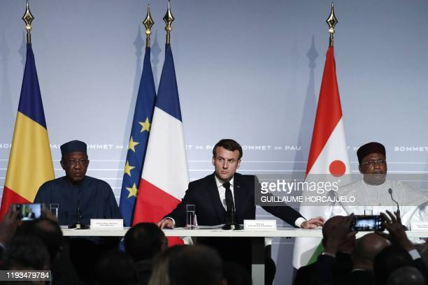 French President Emmanuel Macron flanked by Niger's President Mahamadou Issoufou and Chad's President Idriss Deby speaks during a press conference as...