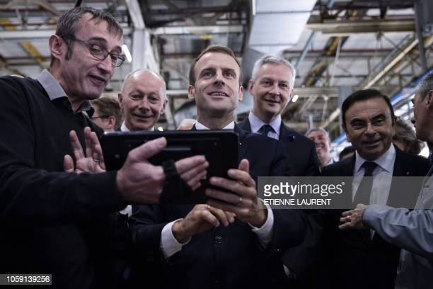 French President Emmanuel Macron flies a drone next to le French Economy Minister Bruno Le Maire and Renault CEO Carlos Ghosn during a visit at the...