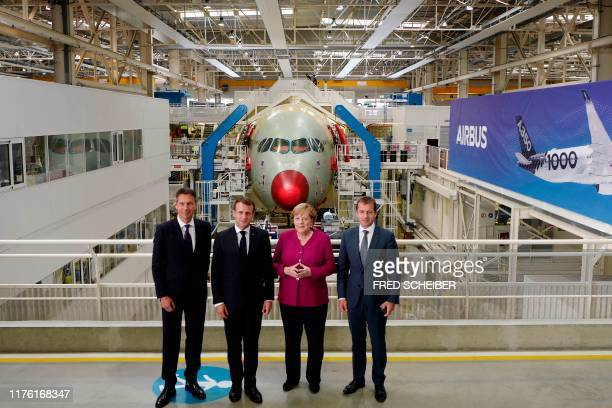 French President Emmanuel Macron German Chancellor Angela Merkel and Airbus CEO Guillaume Faury pose during a visit at the assembly line of the...