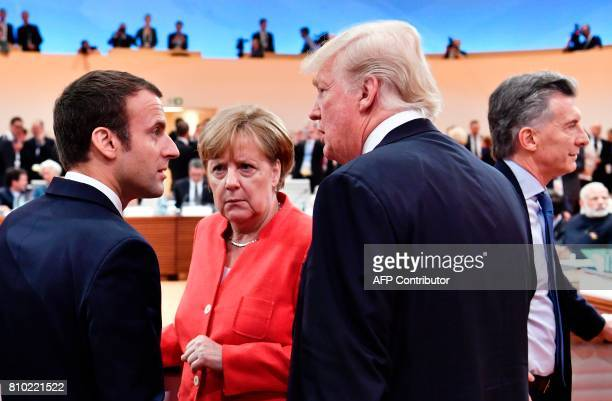 French President Emmanuel Macron German Chancellor Angela Merkel and US President Donald Trump confer as Argentinia's President Mauricio Macri walks...