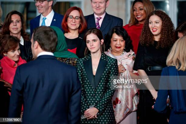 French President Emmanuel Macron gestures as he joins others including British actress Emma Watson as they pose during a family photograph following...