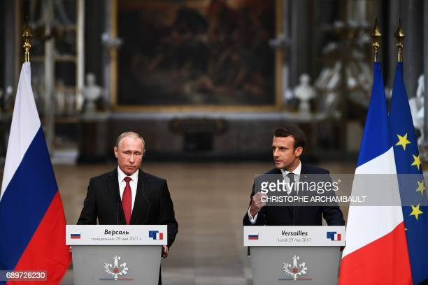 TOPSHOT French President Emmanuel Macron gestures as he speaks during a joint press conference with Russian President Vladimir Putin following their...