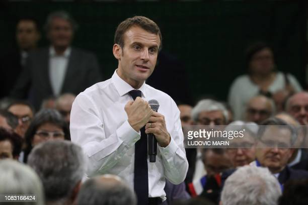 French President Emmanuel Macron gestures as he speaks during a meeting gathering some 600 mayors who will relay the concerns aired by residents in...