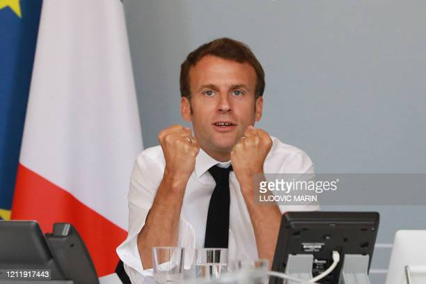 French President Emmanuel Macron gestures as he takes part in a videoconference with artists from different fields at the Elysee Palace in Paris on...