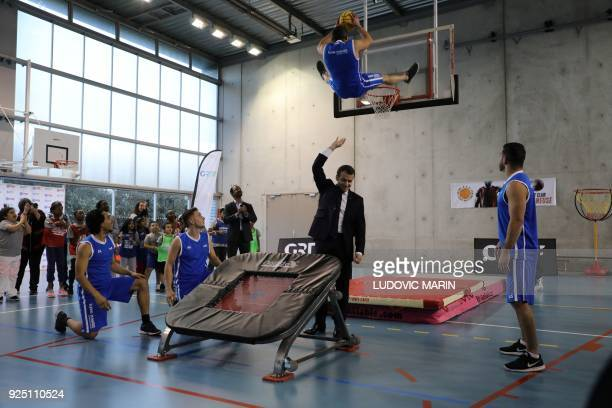 French President Emmanuel Macron gestures as he takes part in display of basketball skills during a visit at the Jesse Owens gymnasium in...