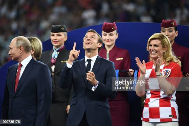 TOPSHOT French President Emmanuel Macron gestures between Croatian President Kolinda GrabarKitarovic and Russian President Vladimir Putin during the...