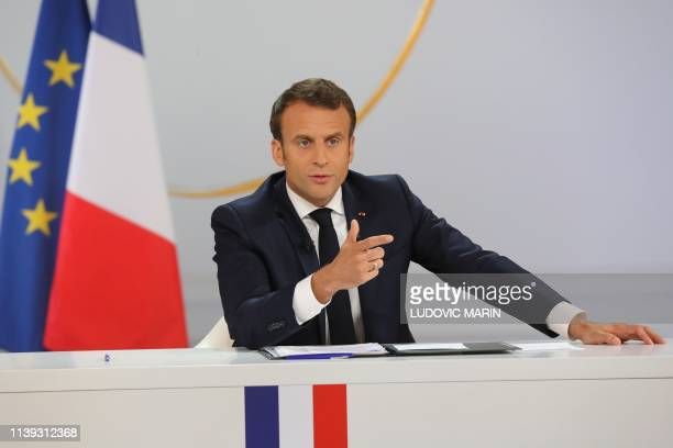 TOPSHOT French President Emmanuel Macron gestures during his live address following the Great National Debate at the Elysee Palace in Paris on April...