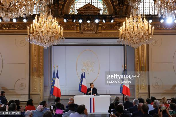 "French President Emmanuel Macron gestures during his live address following the ""Great National Debate"", at the Elysee Palace in Paris on April 25,..."