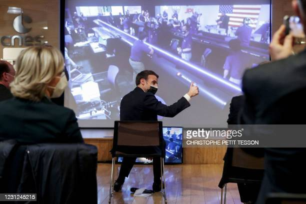 French President Emmanuel Macron gives the thumb-up as he sits in front of a screen broadcasting the landing of NASAs Perseverance Mars rover on the...