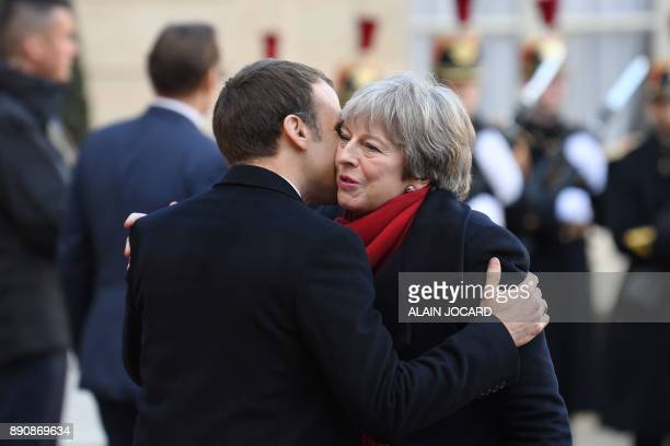 French President Emmanuel Macron greets Britain's Prime Minister Theresa May as she arrives at the Elysee palace on December 12 2017 in Paris for a...