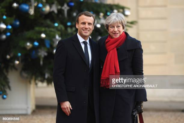French President Emmanuel Macron greets Britain's Prime Minister Theresa May upon her arrival at the Elysee palace on December 12 2017 in Paris for a...
