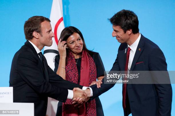 French President Emmanuel Macron greets Executive President of the Paris delegation Tony Estanguet as Mayor of Paris Anne Hidalgo looks on during a...