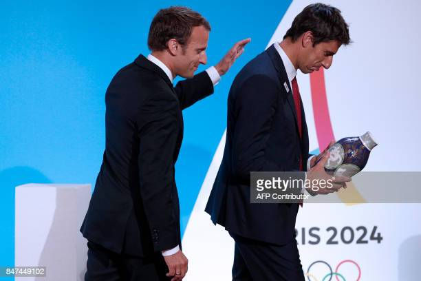 French President Emmanuel Macron greets Executive President of the Paris delegation Tony Estanguet after speaking during a ceremony at the Elysee...