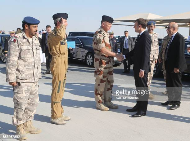 French President Emmanuel Macron greets French General Frederic Parisot near Foreign Minister JeanYves Le Drian upon their arrival at the alUdeid Air...