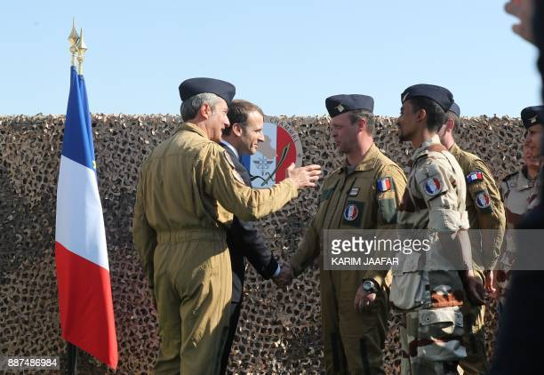 French President Emmanuel Macron greets French troops stationed at the alUdeid Air Base in the Qatari capital Doha on December 7 2017 / AFP PHOTO /...