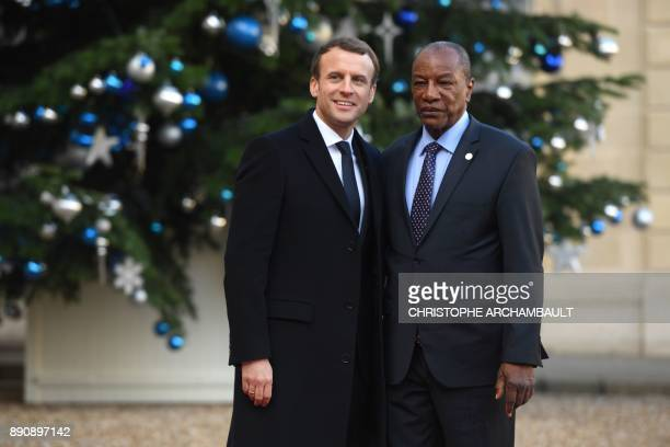 French President Emmanuel Macron greets Guinean President Alpha Conde arriving at the Elysee palace on December 12 2017 in Paris for a lunch hosted...