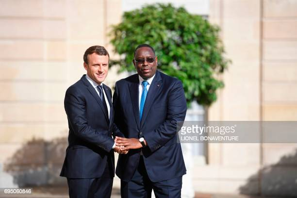 French President Emmanuel Macron greets his Senegalese counterpart Macky Sall upon his arrival for their meeting at the Elysee palace on June 12 2017...