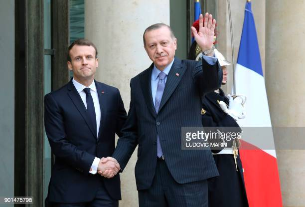 French President Emmanuel Macron greets his Turkish counterpart Recep Tayyip Erdogan upon his arrival for their meeting and luncheon on January 5...